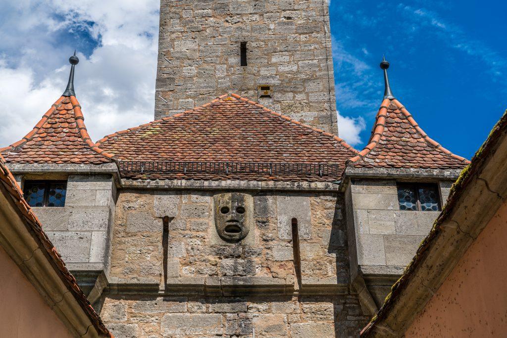 Máscara no alto do portão Burgtor em Rothenburg